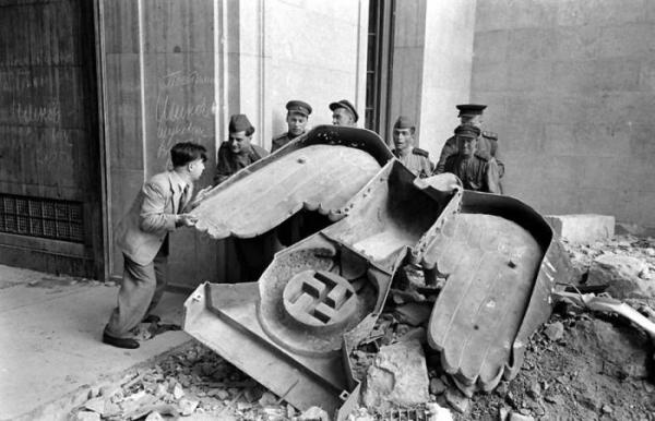 Uno de los símbolos nazis derribado en el suelo tras el bombardeo de los aliados sobre Berlín