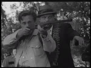 Fotograma en el que se ve a uno de los hombres del comisario McClellan disparando contra Ben, asomado a una de las ventanas de la casa